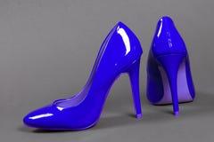 Sapatas azuis dos saltos altos no fundo cinzento Imagens de Stock Royalty Free