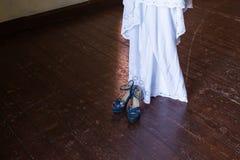 Sapatas azuis nupciais em um fundo de madeira e em uma peça do vestido de casamento rústico fotografia de stock royalty free