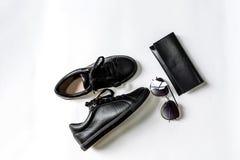 Sapatas, bolsa e ?culos de sol pretos com lentes pretas em um fundo claro foto de stock