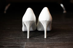Sapatas brancas da dama de honra com os cristais de rocha no assoalho Fotos de Stock Royalty Free