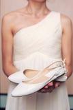 Sapatas brancas nas mãos da noiva imagens de stock royalty free