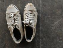 Sapatas brancas sujas e velhas na terra suja do cimento imagens de stock royalty free