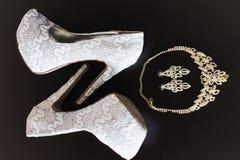Sapatas, brincos e colar da dama de honra na tabela Fotografia de Stock