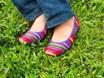 Sapatas com o pano andino colorido na grama Fotos de Stock