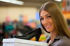 Sapatas da compra da mulher na loja Foto de Stock Royalty Free