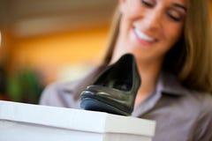 Sapatas da compra da mulher na loja Fotografia de Stock