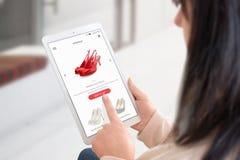 Sapatas da compra da mulher em linha com tabuleta imagem de stock royalty free