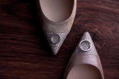 Sapatas da forma da noiva com as gemas com alianças de casamento no fundo de madeira Vista superior Configuração lisa fotografia de stock