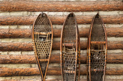 Sapatas da neve e uma cabana rústica de madeira Fotos de Stock Royalty Free