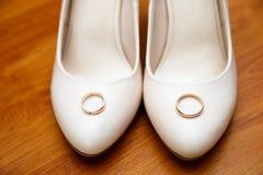 Sapatas das noivas com uma aliança de casamento do ouro nela fundo de madeira Imagem de Stock Royalty Free