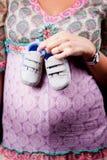 Sapatas de bebê da terra arrendada da mulher gravida fotografia de stock royalty free
