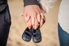 Sapatas de bebê da terra arrendada da mulher gravida foto de stock