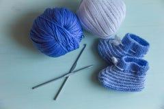 Sapatas de bebê de confecção de malhas com fio azul e branco Fotografia de Stock Royalty Free