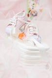 Sapatas de bebê e pacifier alaranjado em tecidos do algodão Fotos de Stock