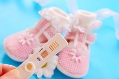 Sapatas de bebê e teste de gravidez Fotografia de Stock