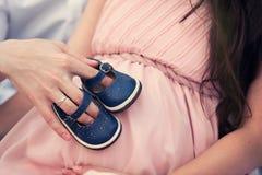 Sapatas de bebê em sua barriga Fotografia de Stock Royalty Free