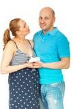 Sapatas de bebê grávidas felizes da terra arrendada dos pares Imagem de Stock