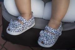 Sapatas de bebê vestindo do pé do bebê no carrinho de criança fotografia de stock