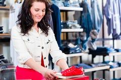 Sapatas de compra da mulher na loja Fotos de Stock Royalty Free