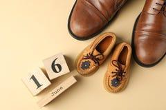 Sapatas de couro de Brown, sapatas das crianças e calendário de madeira no fundo da cor, espaço para o texto fotografia de stock