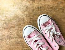 Sapatas de lona cor-de-rosa no fundo de madeira, sapatas da mulher imagem de stock