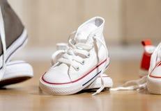 Sapatas de lona das sapatilhas dos pais e da criança no assoalho de madeira em casa em esperar uma família feliz do bebê imagens de stock