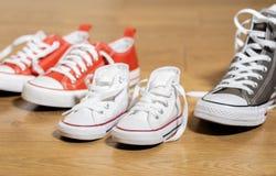 Sapatas de lona das sapatilhas dos pais e da criança no assoalho de madeira em casa em esperar uma família feliz do bebê imagens de stock royalty free