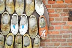 Sapatas de madeira holandesas velhas em uma parede de tijolo do vintage Foto de Stock