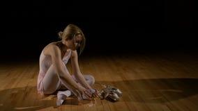 Sapatas desatando da bailarina loura e assento em um assoalho cansado filme