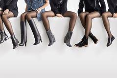 Sapatas diferentes nos pés fêmeas Imagens de Stock