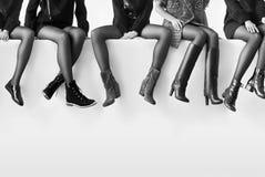 Sapatas diferentes nos pés fêmeas Fotografia de Stock