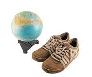 Sapatas do esporte ao lado de um globo Imagens de Stock Royalty Free