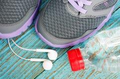 Sapatas do esporte com fones de ouvido e água potável Fotografia de Stock
