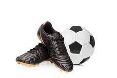 Sapatas do futebol e um futebol fotografia de stock royalty free