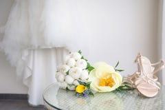 Sapatas do ramalhete e da noiva do casamento, no vestido da noiva do fundo imagens de stock royalty free