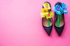 Sapatas do salto alto do ` s da mulher com flores de papel para dentro no fundo cor-de-rosa, vista superior Fotos de Stock Royalty Free