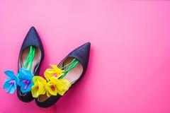 Sapatas do salto alto do ` s da mulher com flores de papel para dentro no fundo cor-de-rosa, vista superior Foto de Stock Royalty Free