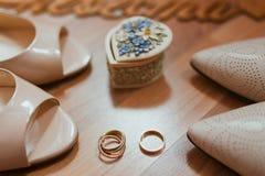 Sapatas e anéis brancos das noivas Foto de Stock