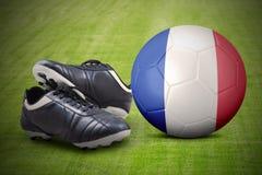 Sapatas e bola do futebol no campo Imagem de Stock Royalty Free