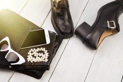 sapatas e calças de brim, smartphone, óculos de sol, pérola em d de madeira branco fotografia de stock royalty free