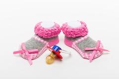 Sapatas e chupetas fêmeas de bebê Fotografia de Stock