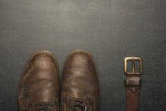Sapatas e correia marrons clássicas na tabela de madeira fotos de stock royalty free