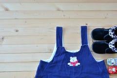 Sapatas e desgaste do bebê ou da criança na opinião de tampo da mesa de madeira sob nat Fotos de Stock Royalty Free