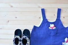 Sapatas e desgaste do bebê ou da criança na opinião de tampo da mesa de madeira sob nat Imagens de Stock