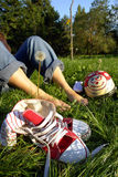 Sapatas e pés desencapados na grama Fotos de Stock