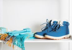 Sapatas, luvas e lenço do inverno na prateleira de madeira branca Fotos de Stock Royalty Free