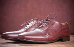 Sapatas marrons clássicas de oxford no fundo de madeira Fotos de Stock