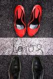 Sapatas masculinas e fêmeas no asfalto, concep do amor Imagem de Stock Royalty Free