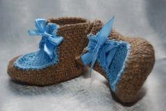 Sapatas minúsculas para um bebê feito com lãs e laço azul fotos de stock