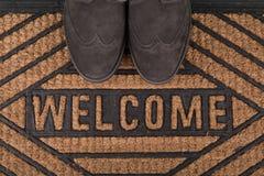 Sapatas no capacho bem-vindo novo no assoalho de madeira Fotos de Stock